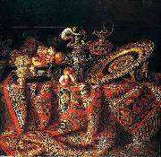 A still life of peaches, grapes and pomegranates in a pewter bowl, an ornate ormolu plate and ewers, all resting on a table draped with a carpet